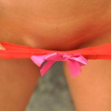 Busty teen Sweet Krissy teases in just a pair of panties with pink ribbons on them